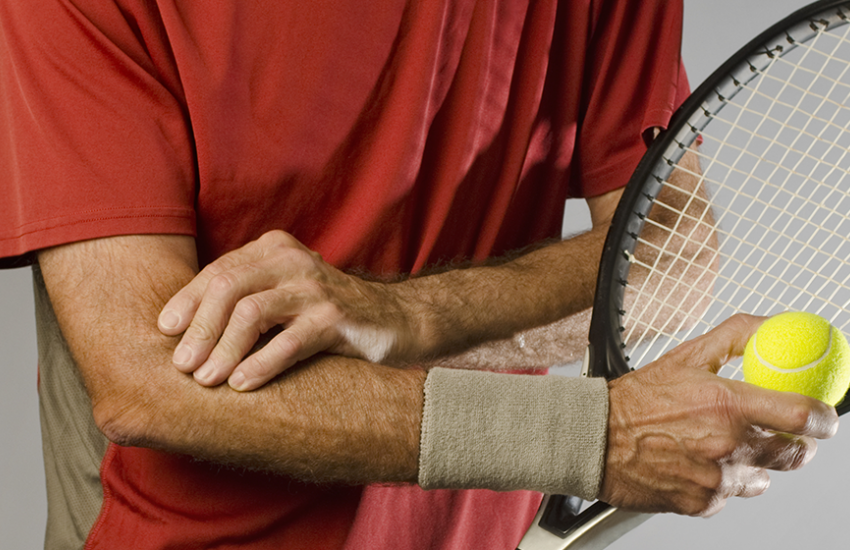 Man rubbing elbow after playing tennis